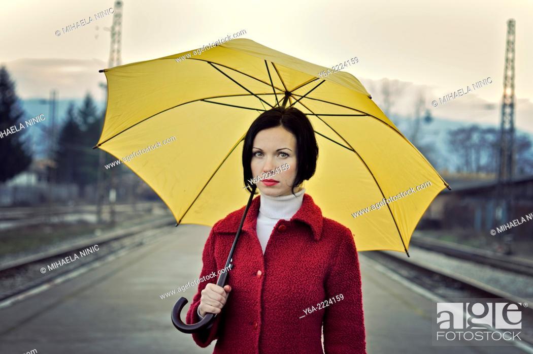 Stock Photo: Woman holding yellow umbrella.