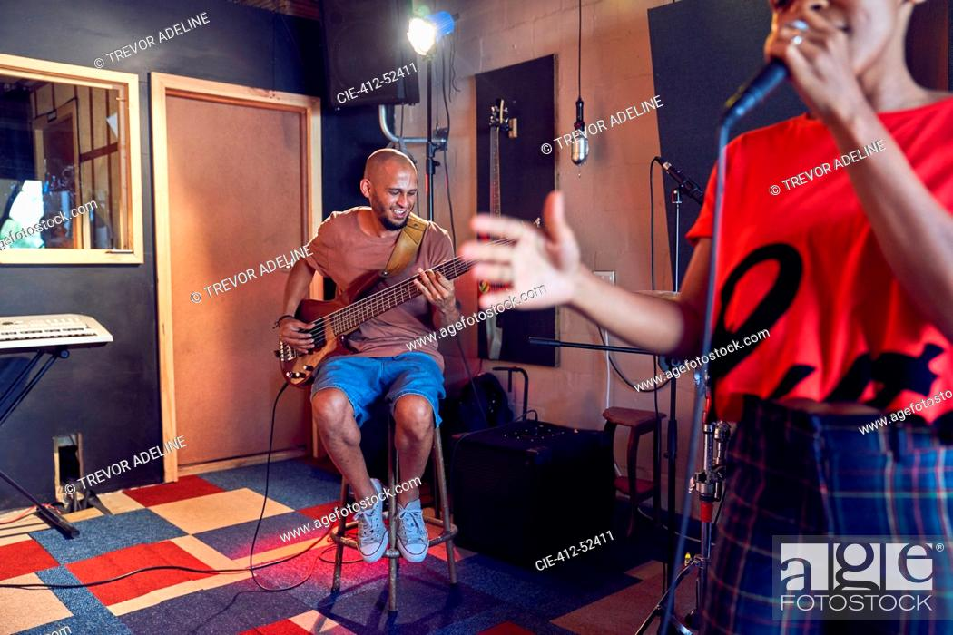 Stock Photo: Musicians singing and playing guitar in recording studio.