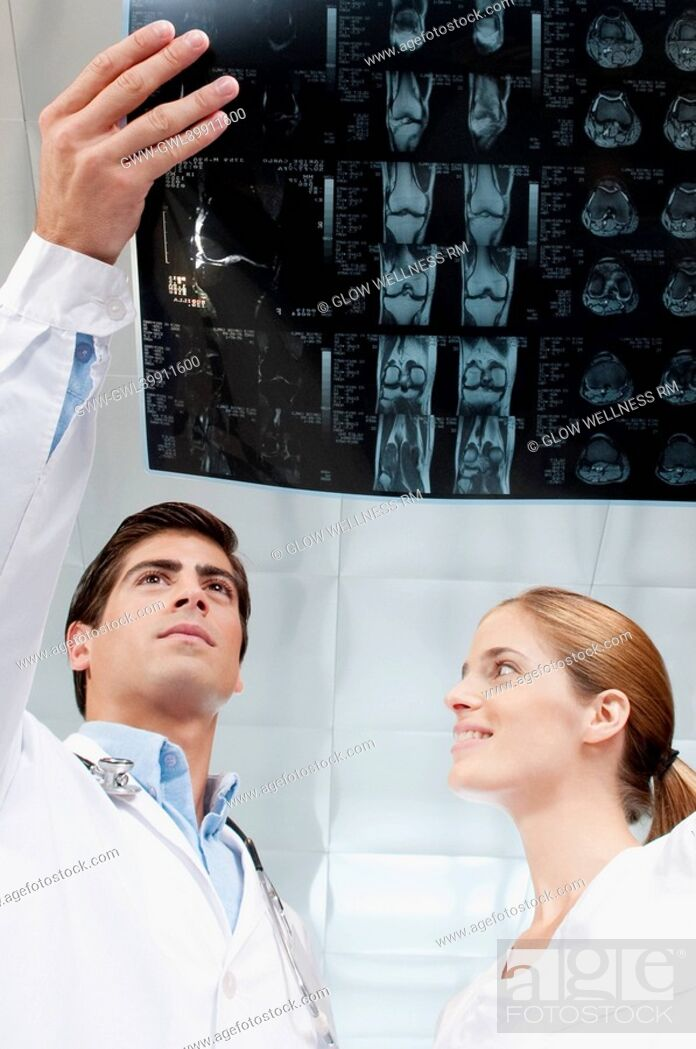 Imagen: Doctor and a female nurse examining an x-ray report.