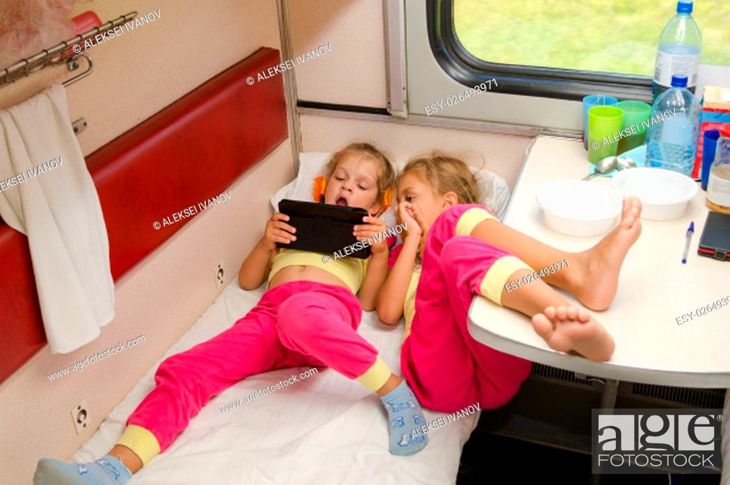 Stock Photo: Two little girls lie on the train with his feet on the lower second-class place car in the same pajamas and looking at tablet.