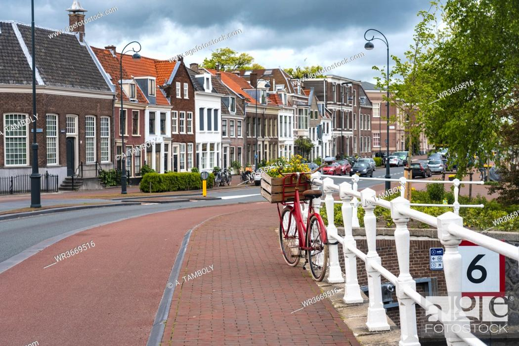 Stock Photo: Netherlands, North Holland, Haarlem, Bicycle parked along railing of canal bridge with houses along Hooimarkt street in background.
