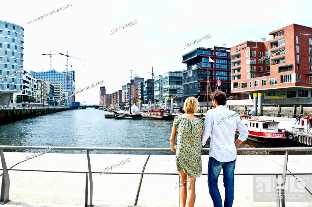 Photo de stock: Couple looking over harbor basin, Magellan-Terraces, HafenCity, Hamburg, Germany.