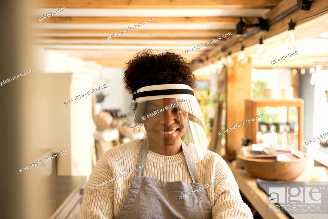 Stock Photo: Portrait happy female shop owner wearing face shield.
