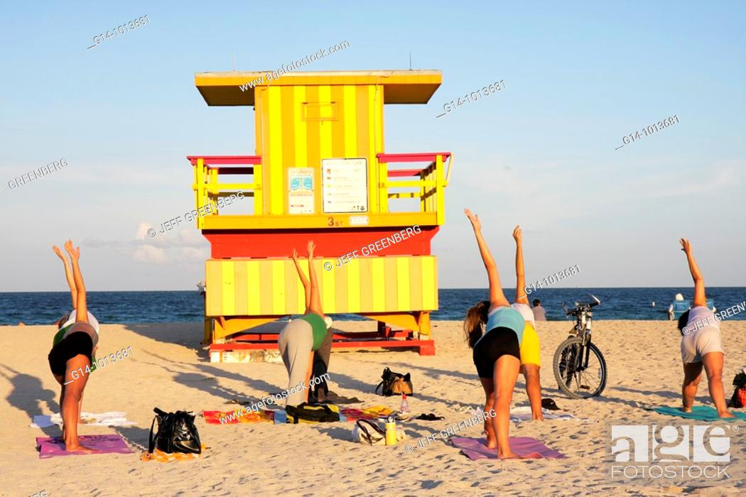 Stock Photo: Florida, Miami Beach, sand, shore, beach, lifeguard stand, station, yoga class, woman, women, exercise, health, fitness, pose, asana, triangle pose,.