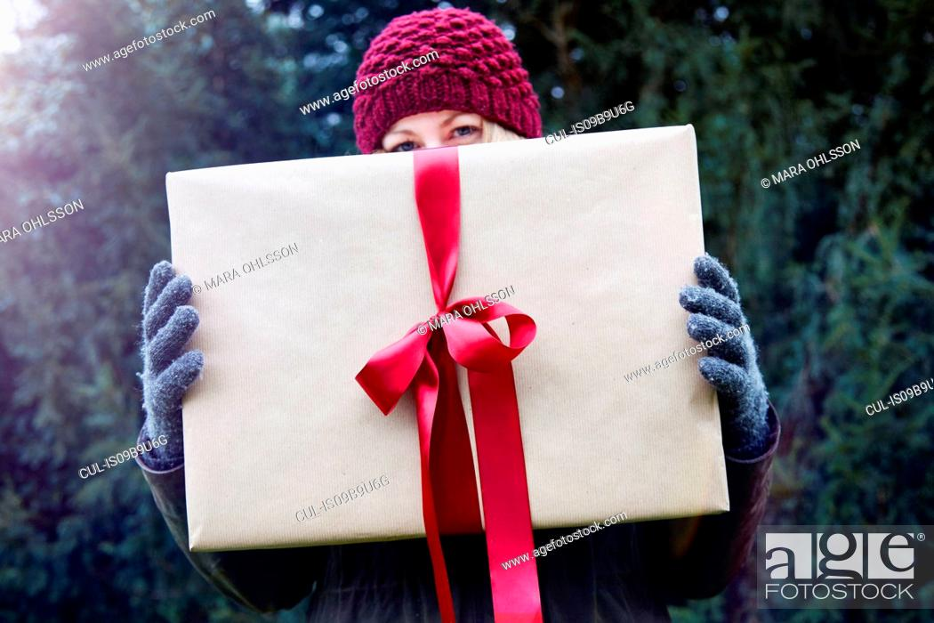 Stock Photo: Woman holding up Christmas present with red ribbon.
