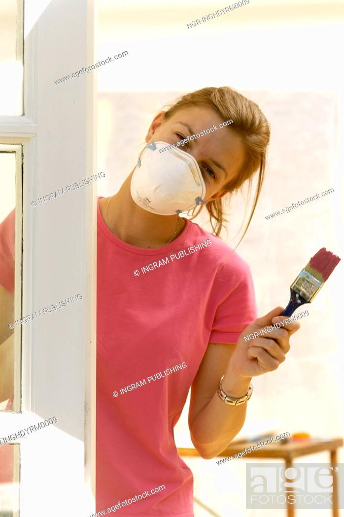 Stock Photo: Close-up of a young woman wearing a protective mask and holding a paintbrush.