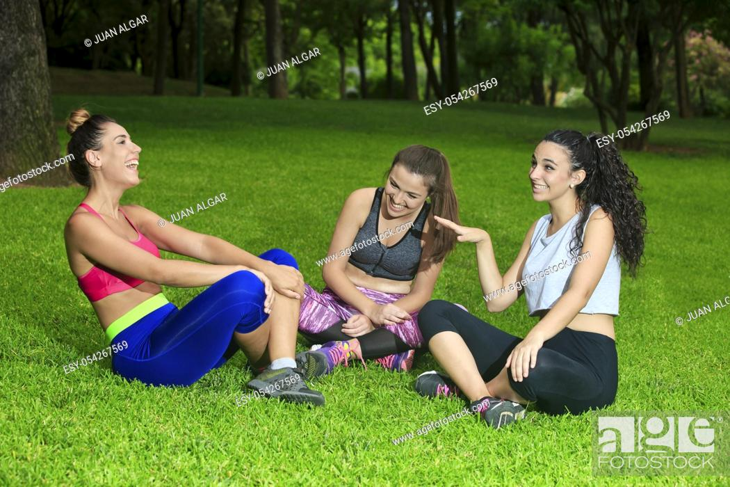 Stock Photo: Three cheerful sportswomen laughing and having fun after workout in park.