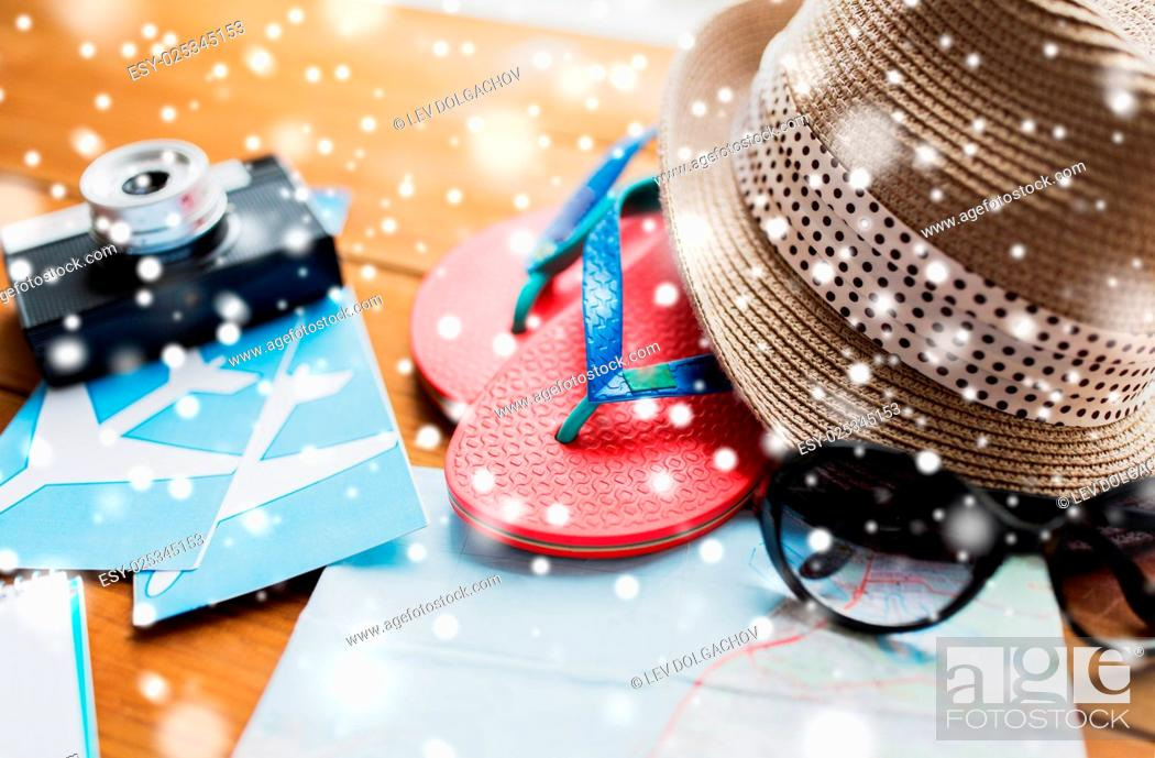 Stock Photo: tourism, winter holidays and objects concept - close up of travel map, flip-flops, hat and camera with airplane tickets on wooden table at home.