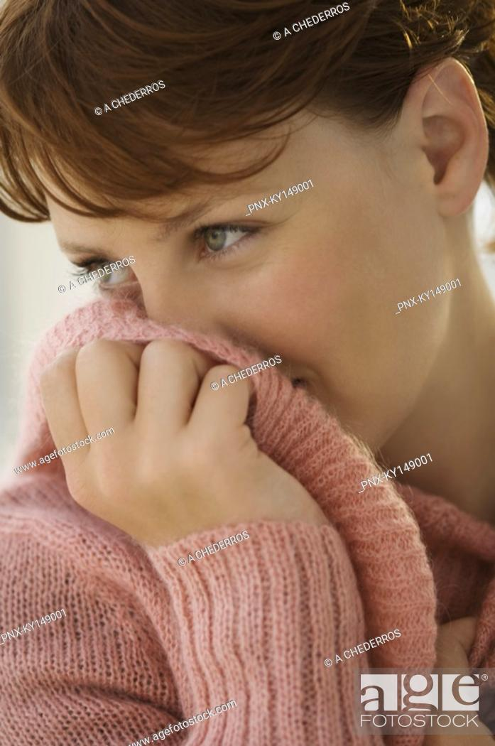 Stock Photo: Portrait of young woman covering her mouth with jumper.