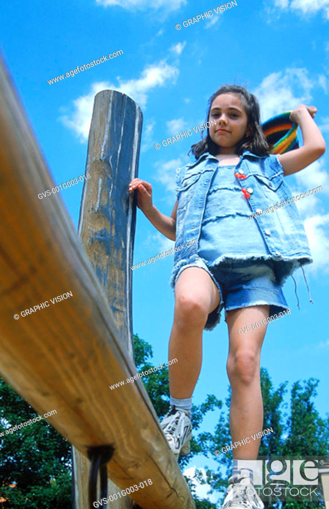 Stock Photo: Young girl walking on a wooden log.