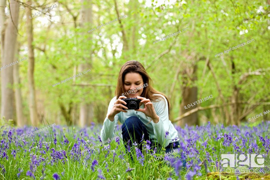 Stock Photo: A young woman photographing bluebells, smiling.