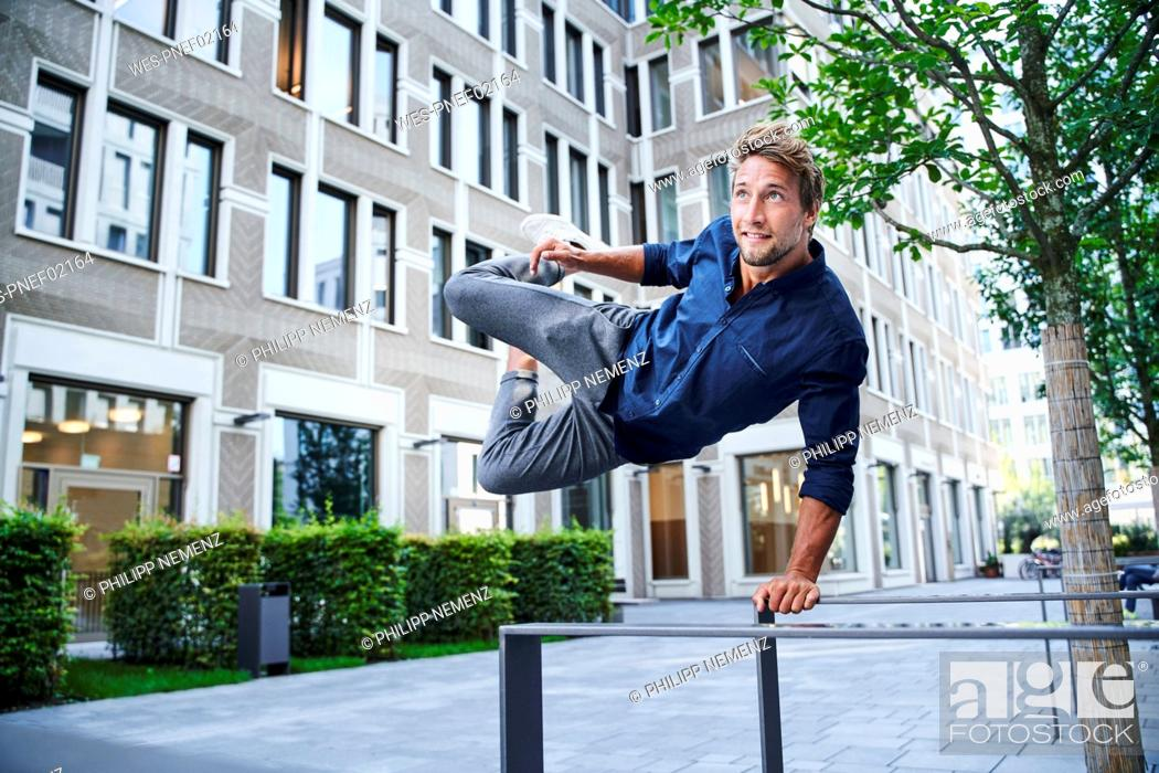 Stock Photo: Young man jumping over railing in the city.