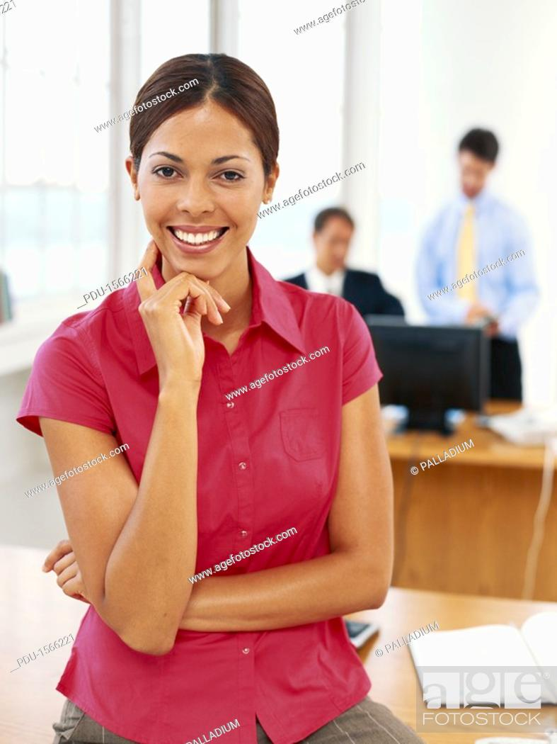 Stock Photo: Businesswoman sitting on desk, smiling.