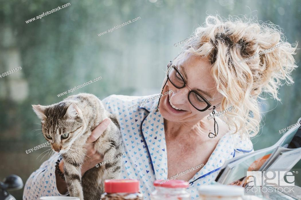 Stock Photo: Blonde young mature woman with glasses in pyjamas at home in breakfast time, reading a magazine and having a moment with his cat.