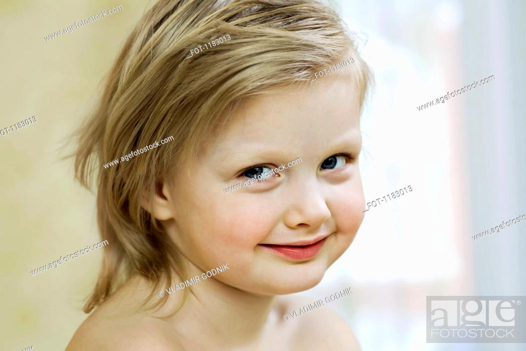 Stock Photo: A young girl smiling slyly.