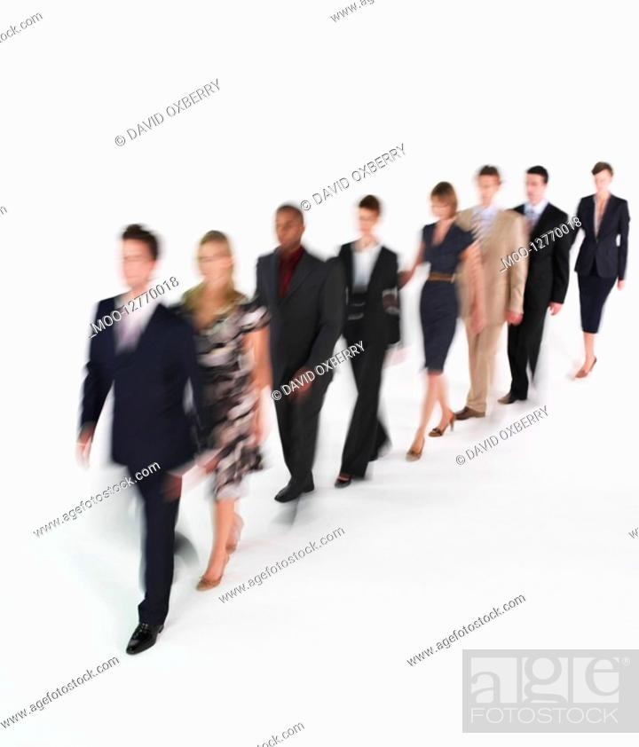 Stock Photo: Line of businesspeople walking blurred effect.