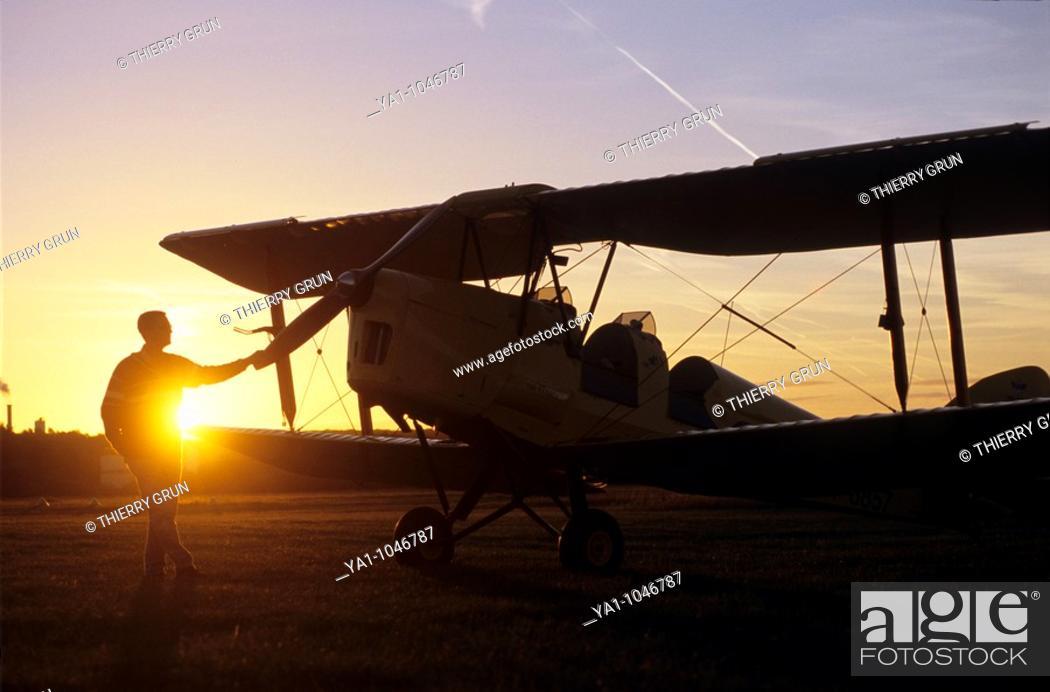 Stock Photo: Pilot near an old trainer biplane De Havilland DH 82a Tiger Moth on sunset.