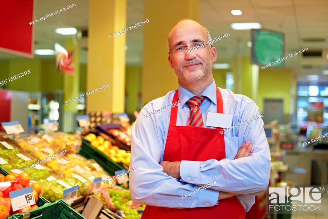 Stock Photo: Germany, Cologne, Mature man standing in supermarket, smiling, portrait.
