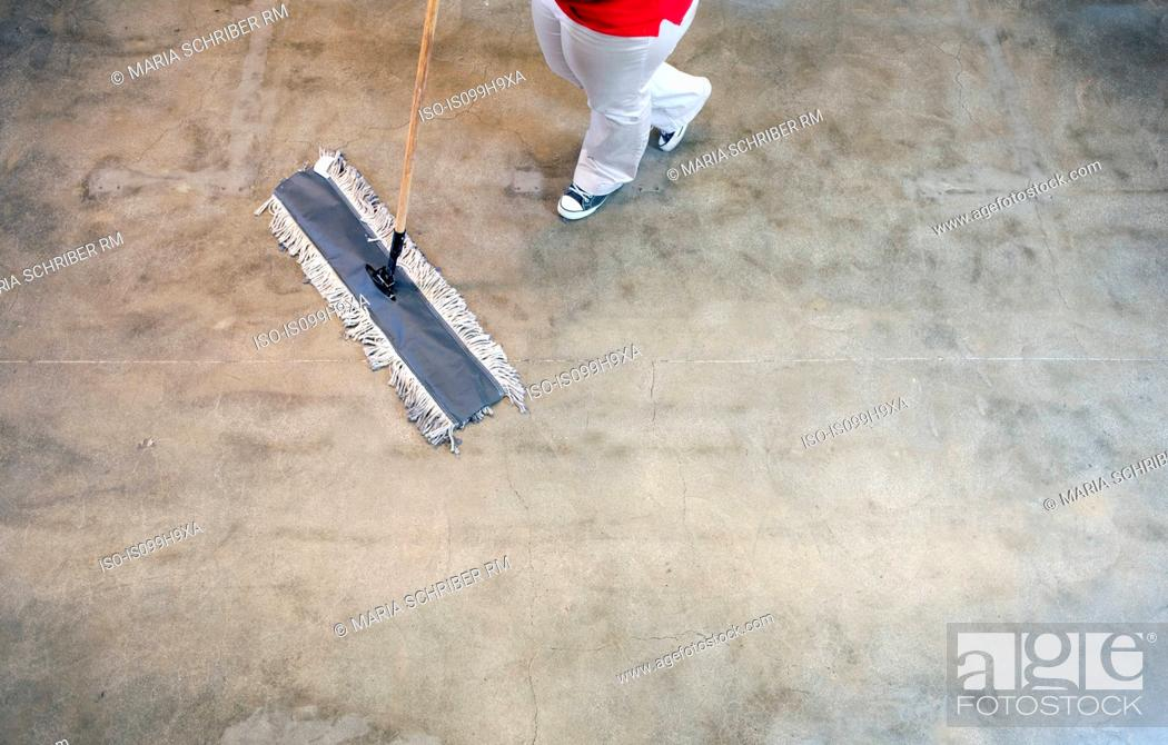 Stock Photo: Young woman sweeping floor, low section.