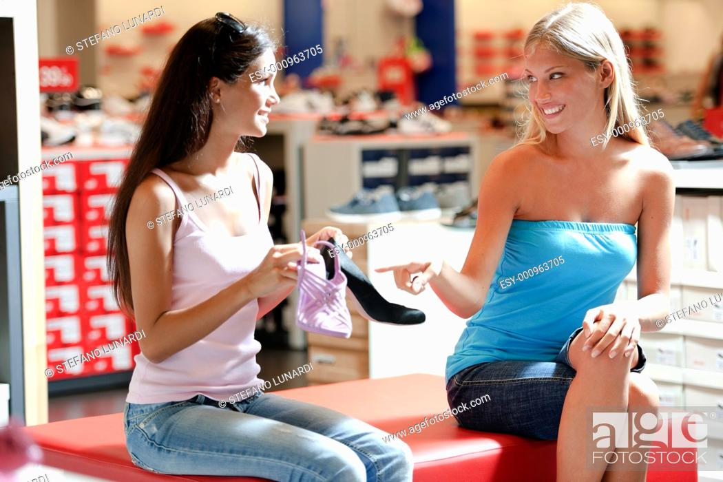 Stock Photo: Female friends purchasing shoes.