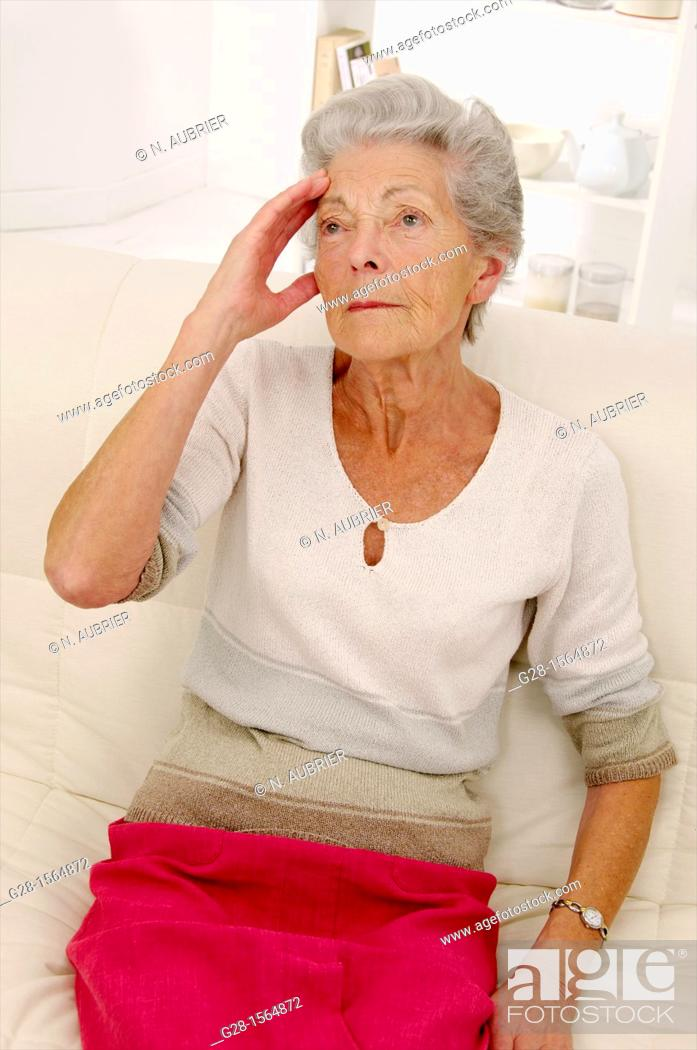 Stock Photo: ALZHEIMER, senior woman holding her forehead and trying to remember her souvenirs.