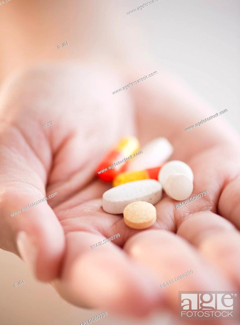 Stock Photo: Hand holding pills and capsules.