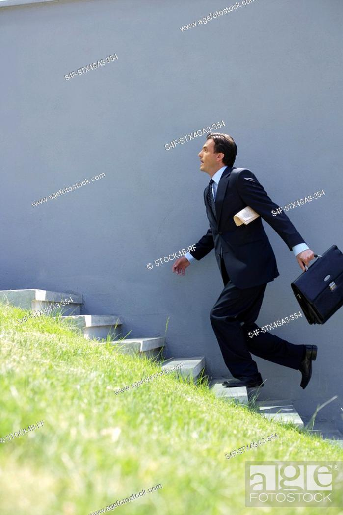 Stock Photo: Businessman running up a stairway.