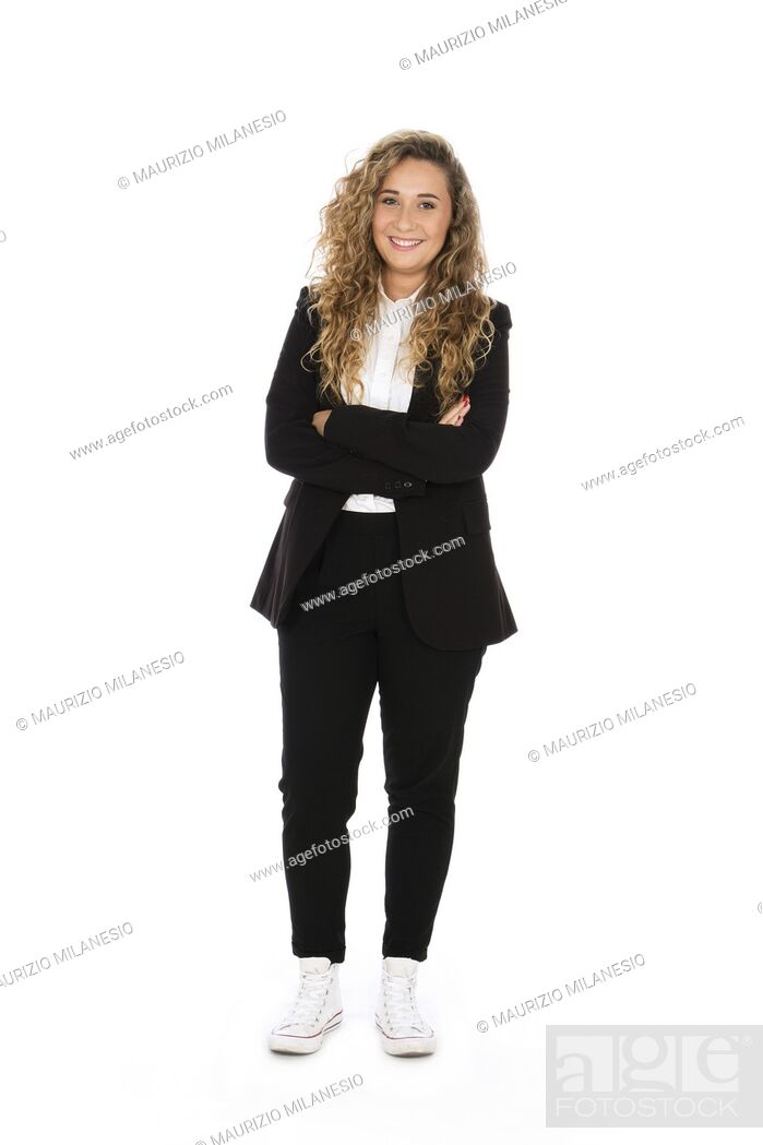 Stock Photo: Smiling girl with curly blonde hair, she is standing with her arms crossed, wearing a black suit and white shirt and sneakers.