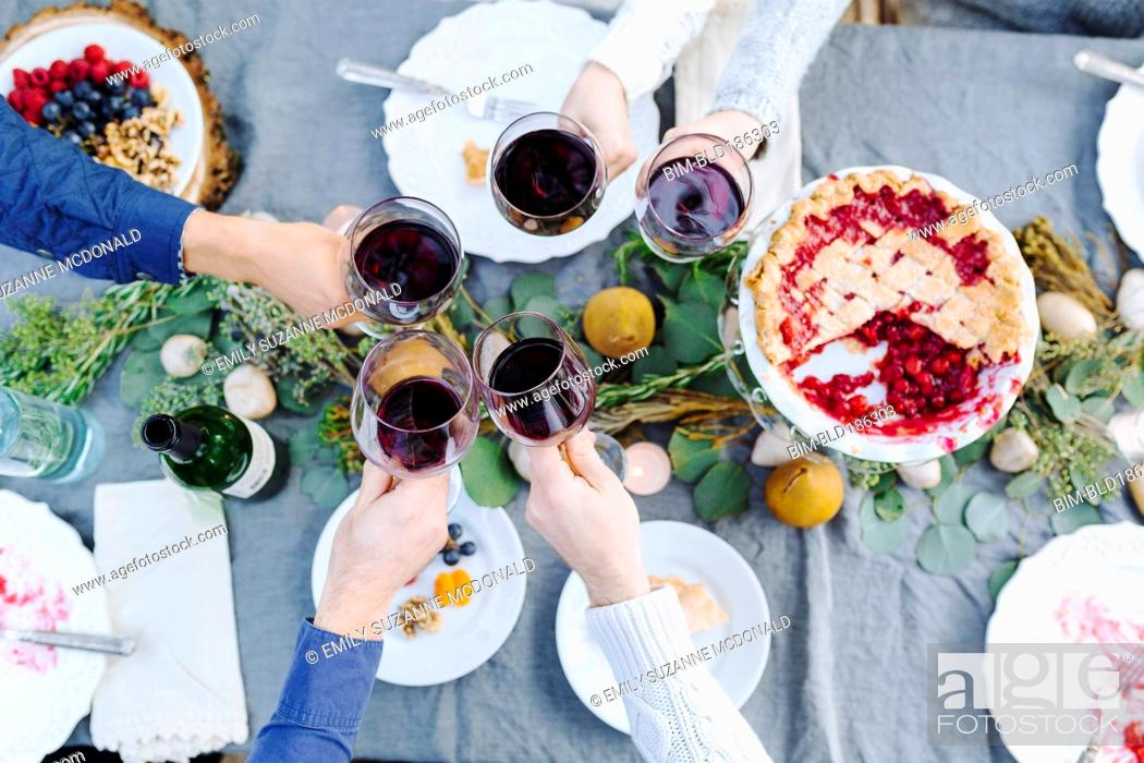 Stock Photo: Friends toasting with wine at outdoor table.