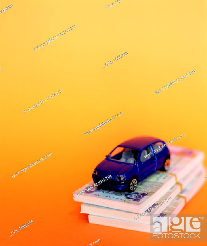 Stock Photo: Toy car on top of pile of UAE money.