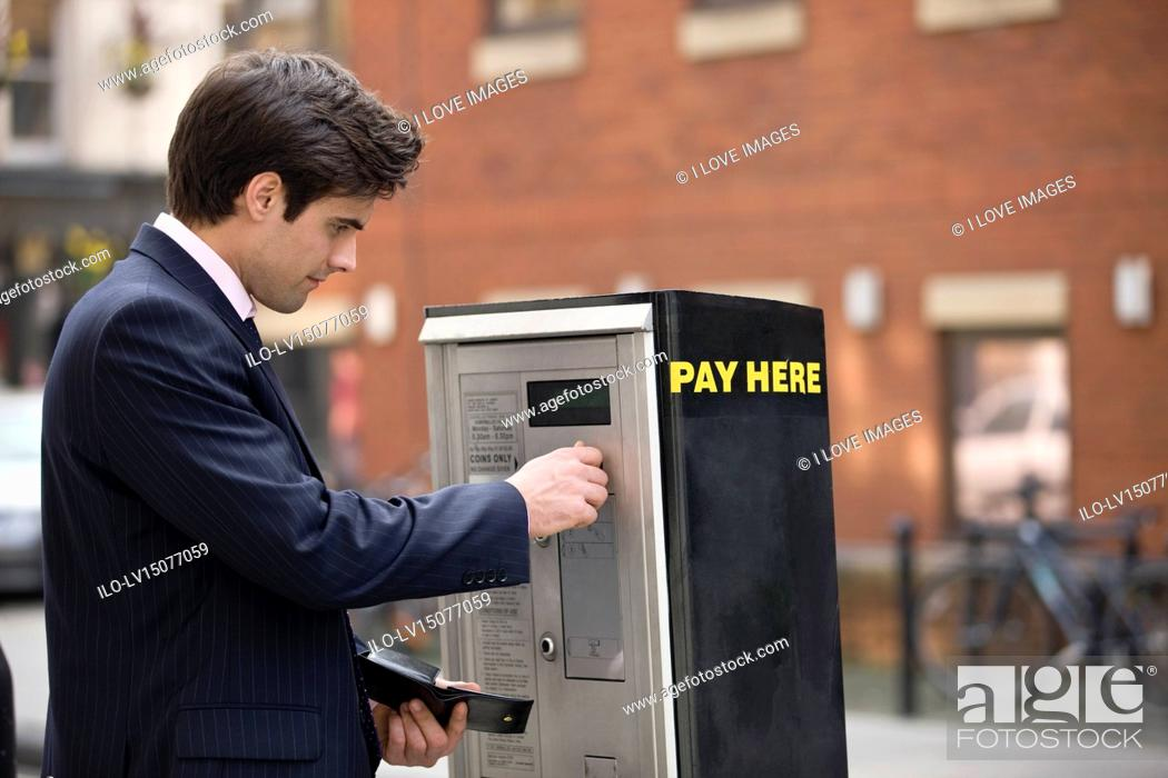 Stock Photo: A businessman putting coins in a parking meter.