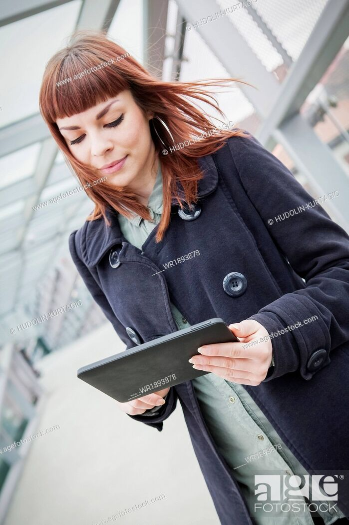 Stock Photo: Young woman in airport building using digital tablet.