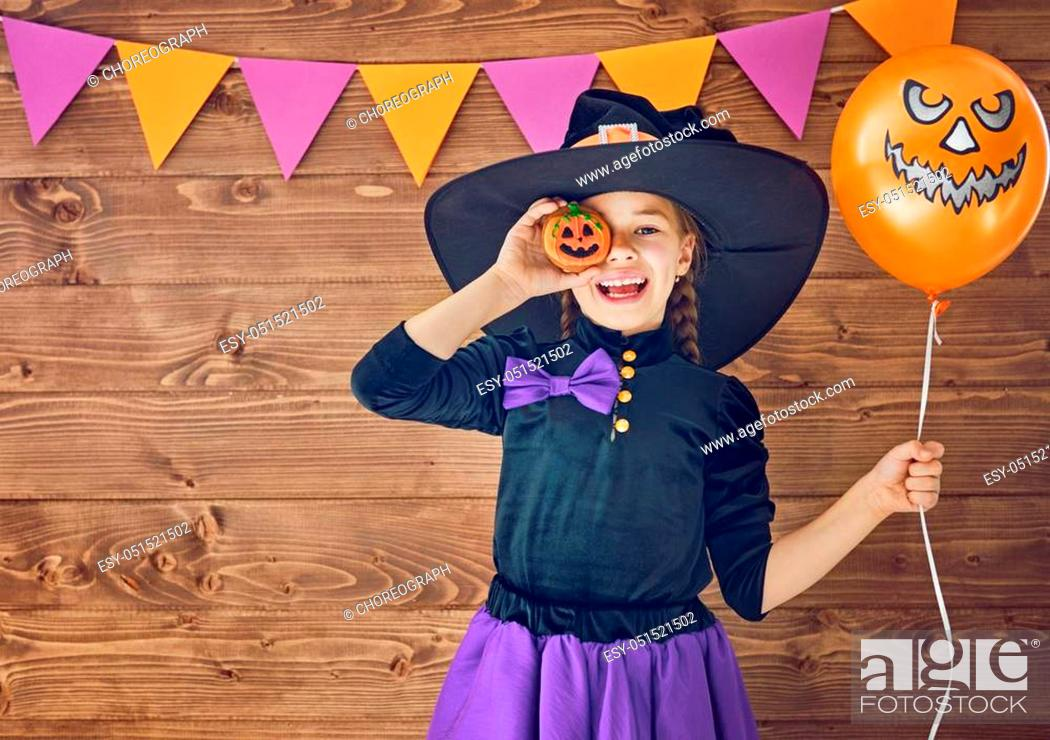 Stock Photo: Happy Halloween! Cute little witch with a pumpkin air balloon.