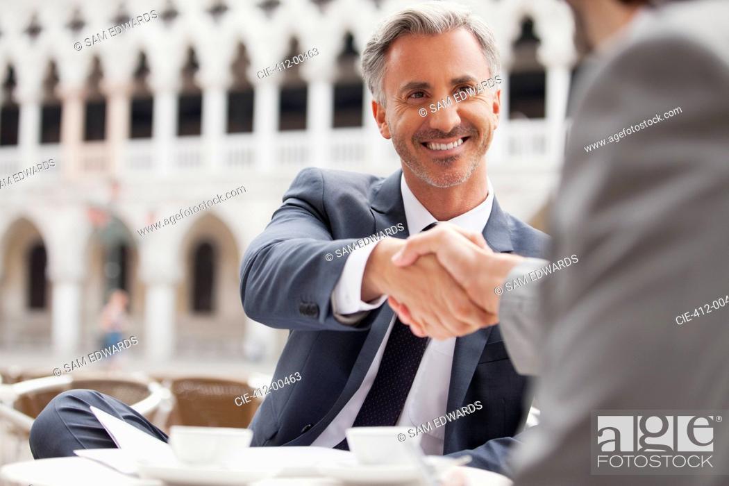 Stock Photo: Smiling businessmen shaking hands at sidewalk cafe.