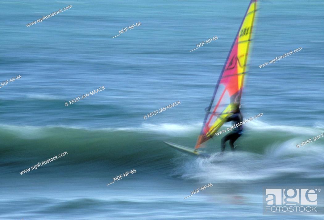 Imagen: Windsurfer riding across a wave.