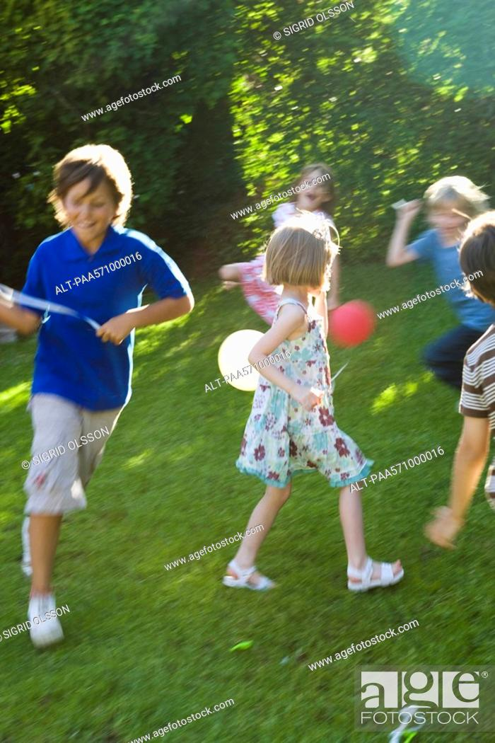 Stock Photo: Children playing outdoors with balloons.
