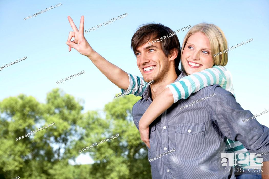 Stock Photo: Germany, Cologne, Young couple embracing, showing peace sign.