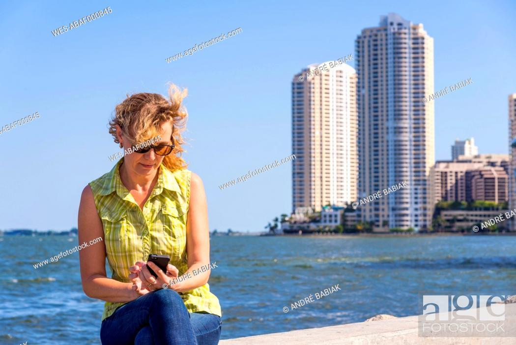 Stock Photo: USA, Florida, Miami, Mature woman sitting on surrounding wall of port and using smartphone.