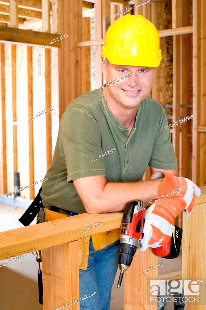 Stock Photo: Builder on site in hardhat, smiling, portrait.
