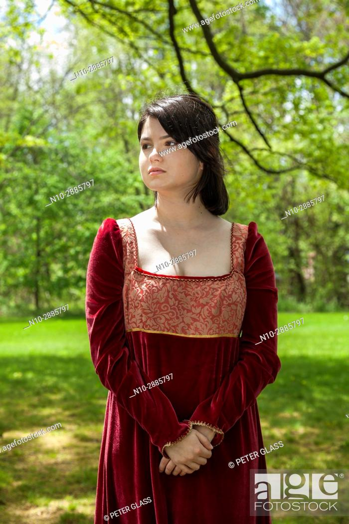 Stock Photo: Young woman, standing in a park, wearing a long red vintage dress.