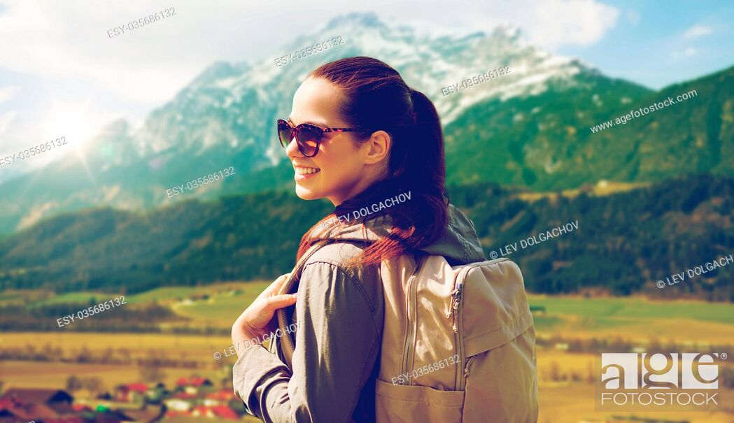 Stock Photo: travel, tourism and people concept - happy young woman with backpack over alps mountains background.