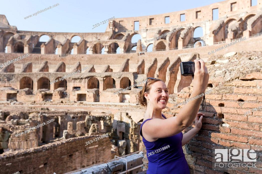Stock Photo: A young female tourist takes a selfie with her camera at the Roman Colosseum; Rome, Italy.