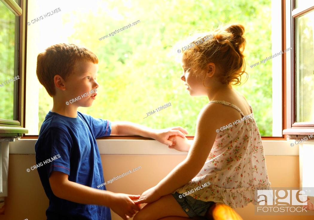 Stock Photo: A brother and sister talking to each other by a window.