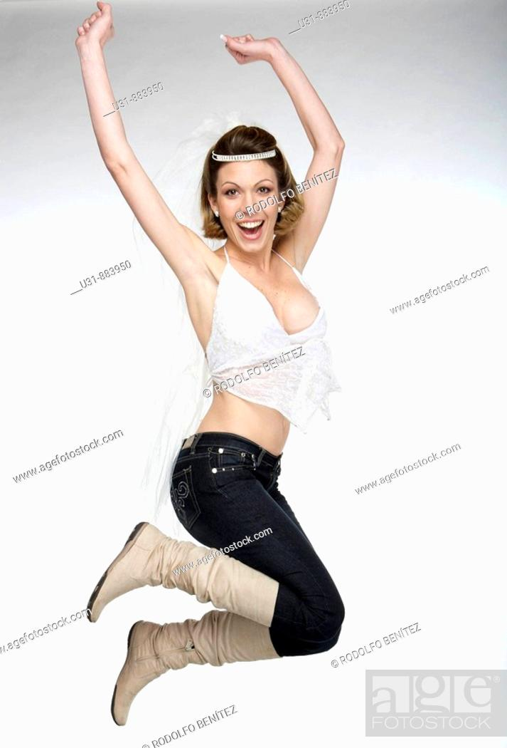Stock Photo: Bride in her 20s wearing jeans and boots under her wedding top celebrates in a studio setting.