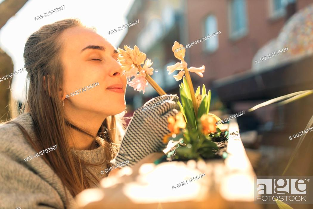 Stock Photo: Young woman smelling at flower in garden.