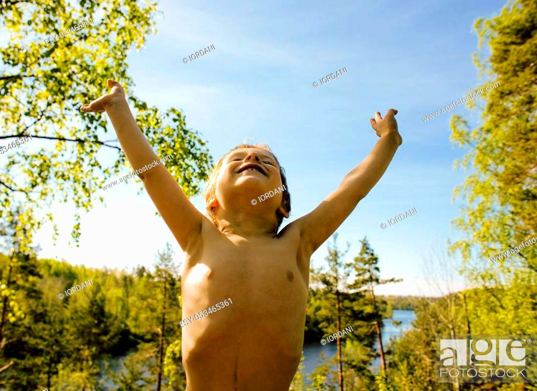 Stock Photo: little cute real boy among tree hight, outdoor lifestyle people concept close up.