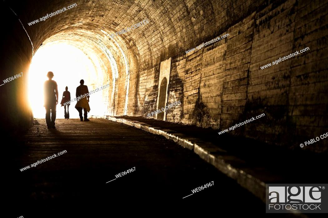 Stock Photo: Three persons coming out from an old tunnel.