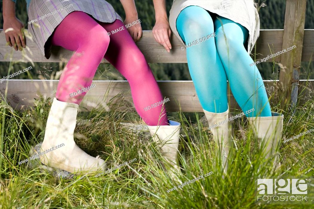 Stock Photo: Girls wearing tights sitting on a fence.