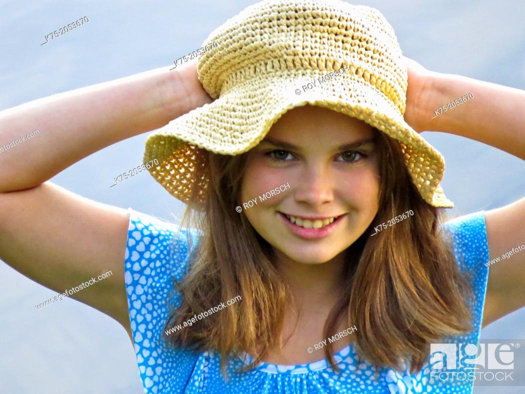 Imagen: Young girl holding her straw hat.