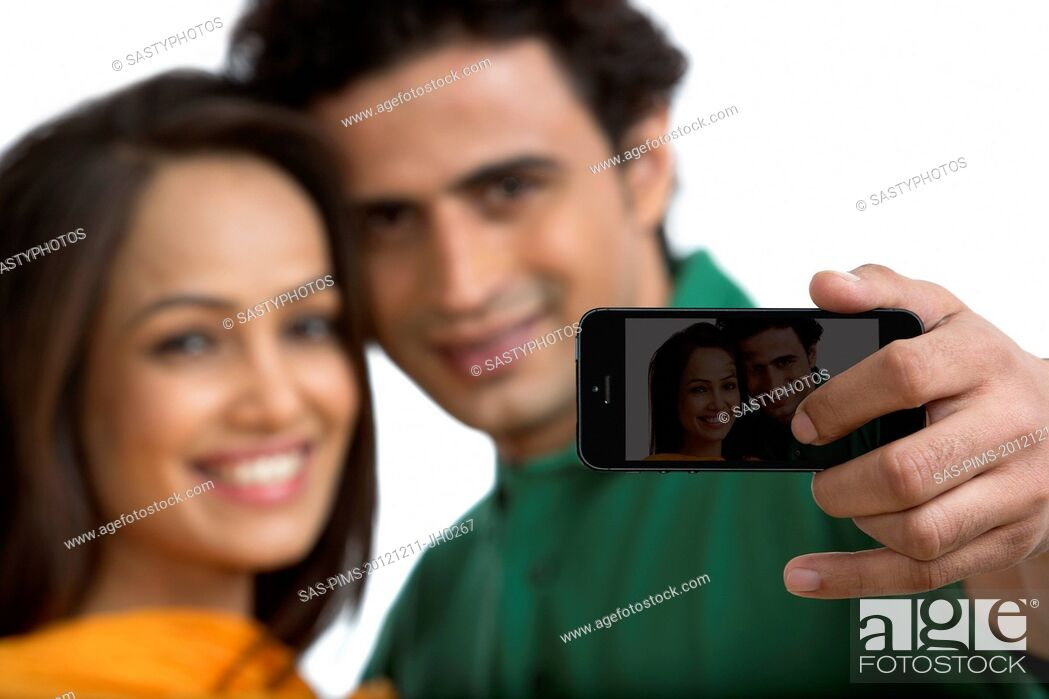 Stock Photo: Couple taking a picture of themselves with a mobile phone.